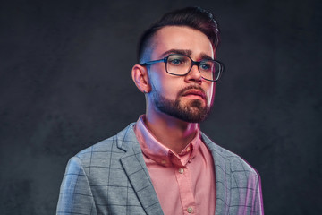Portrait of attractive pensive man in checkered blazer, pink shirt and glasses.