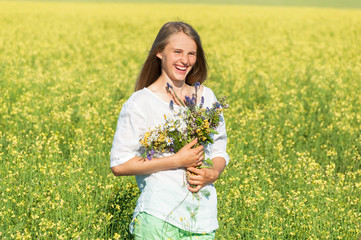 Pretty girl with a bouquet in the field