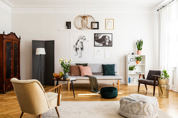 Stylish beige armchair and pouf on the cozy carpet in classy living room interior with grey settee and vintage furniture