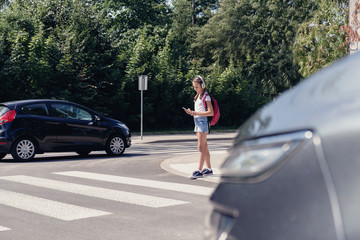 Schoolgirl with headphones and mobile phone on pedestrian crossing in front of a car