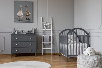 Stylish grey baby room interior with wooden furniture, white scandinavian ladder and teddy bear on pouf, real photo with copy space on the empty wall