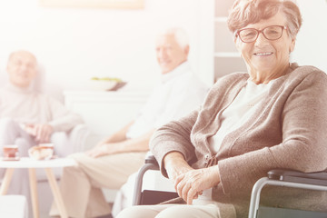 Smiling grandmother in the wheelchair in the nursing house and senior people