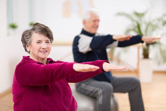 Elderly woman exercising during pilates for seniors in retirement home
