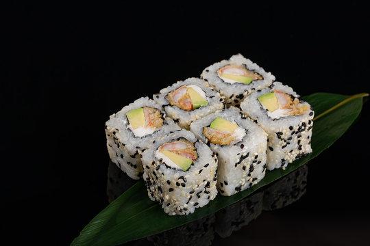 Closeup view of Japanese sushi shrimp tempura roll on banana leaf at black background.