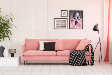 Gallery of posters on white wall in fashionable living room interior with pink couch and industrial lamp