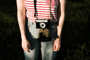 Woman is holding an anlog camera.