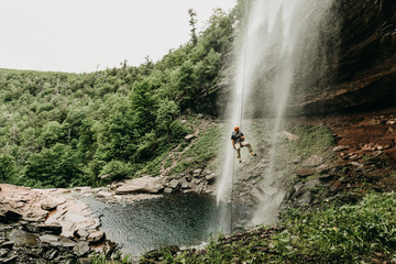Man rappelling waterfall in Catskills, New York State, USA