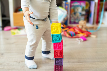 Cute adorable caucasian baby boy playing colorful toys at home. Happy child having fun building tower of soft rubber cubes. Children development and hapy chilldhood concept