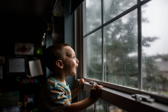 excited boy looking out a window with raindrops at a stormy sky