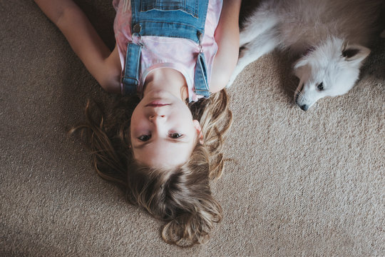 Overhead view of young girl lying on carpet floor with white dog
