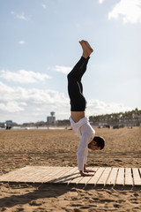 Man doing Yoga on the beach at sunset