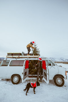Couple decorating van for Christmas
