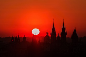 Canvas Prints Cuban Red Red sky and white sun during morning sunrise in Prague, capital of the Czech Republic, sun shining above black horizon towers and spires, urban landscape