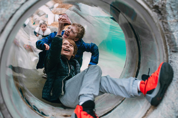 Kids in tunnel smiling at otter swimming at zoo