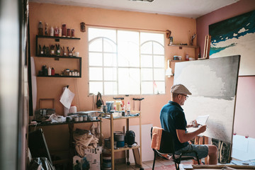 Mid adult man working as painter with brush and canvas in his studio