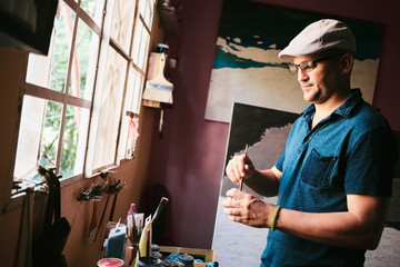 Mid adult male Cuban artist mixing paint with brush in his workshop