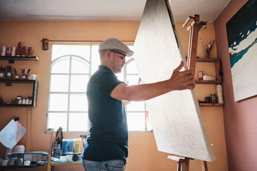 Mid adult man working as painter holding canvas on easel in his studio