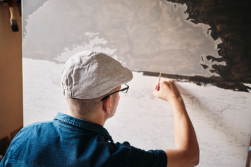 Mid adult Cuban artist painting with brush on canvas in his studio