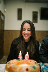 woman is smiling in front of a cake with candles of her 40th birthday