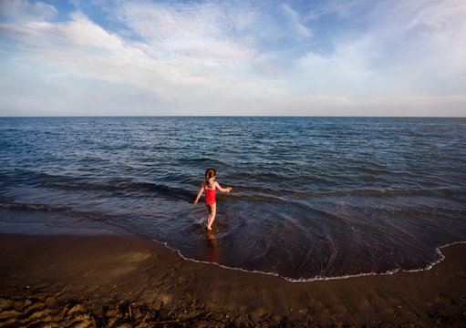 Girl in red walks into sea at beach carrying spade of sand in summer