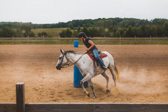 teen girl riding horse around barrel in arena
