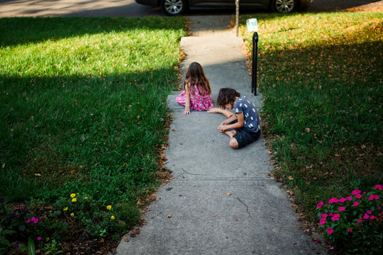 a brother and sister sit barefoot in their yard in summer