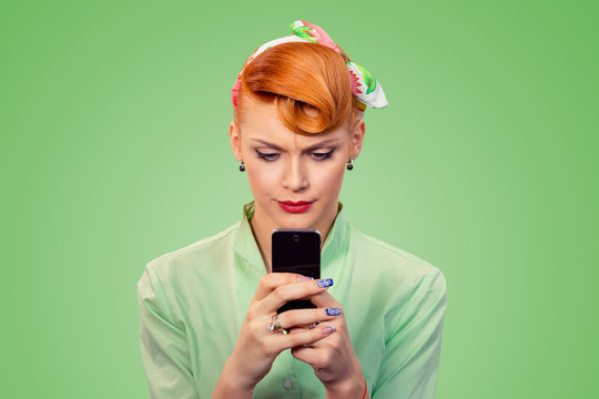 displeased woman looking at texting on phone