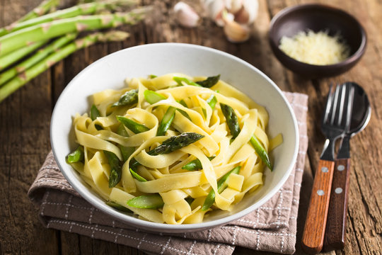 Fresh homemade pasta dish of fettuccine or tagliatelle, green asparagus, garlic and lemon juice in bowl (Selective Focus, Focus on the asparagus head in the middle)