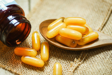 Royal jelly capsules in wooden spoon and sack background / Yellow capsule medicine or supplementary food