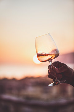 Glass of rose wine in man'€™s hand with sea view and sunset at background, close-up. Summer evening relaxed mood concept