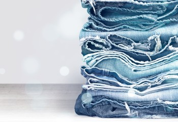 Stack of jeans clothes on background