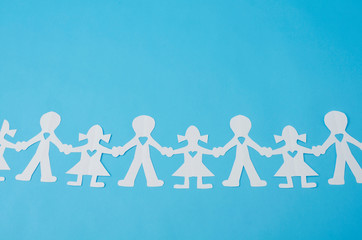 Paper doll chain against blue background. Paper doll chain made from white paper on blue background