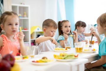 Group of preschool kids have a lunch in daycare. Children eating healthy food in kindergarten