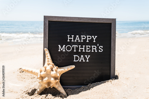 Happy Mothers day beach background with black board and starfish