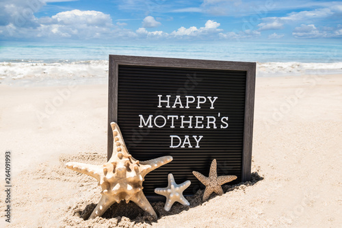 Happy Mothers day beach background with black board and starfishes