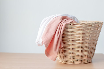 white and pink clothes in laundry basket with copy space on table..
