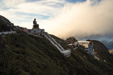 Giant buddha statue on the top of Fansipan mountain peak, Backdrop Beautiful view blue sky and cloud in Sapa, Vietnam. Buddha statue on top at sunset in the clouds.