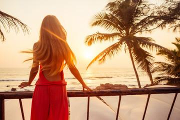 Obraz Portrait long hair blonde beauty stunning sexy model in a stylish pink jumpsuit palm tree and sunset - fototapety do salonu