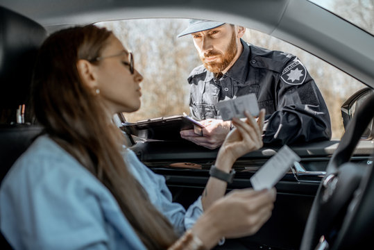 Policeman checking documents of a young female driver sitting in the car, view from the car interior