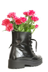 Bunch of pink roses in black combat boot