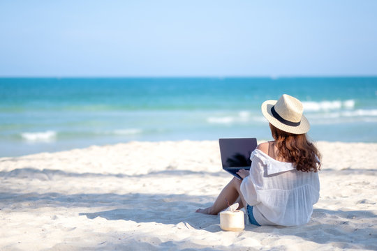 A woman using and typing on laptop computer keyboard while sitting on a beautiful beach