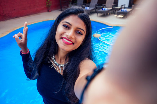beautiful indian woman toothy white smile selfie portrait on smartphone camera summer cafe by sea by the swimming pool goa