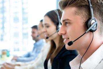 Smiling friendly man working in call center office with team