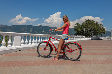 Young woman sitting on bicycle on the seaside promenade. Cheerful girl riding bike at the waterfront on a summer day