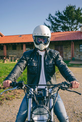 Young man with helmet riding a custom motorbike outdoors