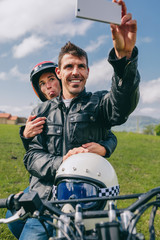 Young couple taking a selfie on the motorcycle outdoors