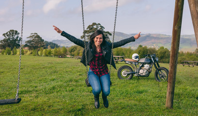 Happy young woman swinging in a recreational area with motorcycle in the background