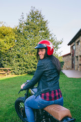 Young woman with helmet riding a custom motorbike outdoors