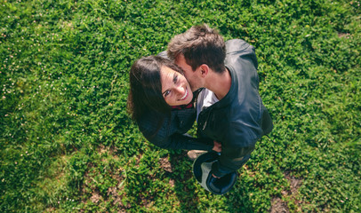 Top view of girl looking at camera hugging her boyfriend while he kisses her outdoors
