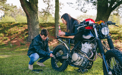 Young man fixing his damaged motorcycle while his girlfriend looks at him taking a beer outdoors